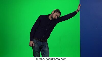 Guy leaning his hand on wall standing against green, screen...