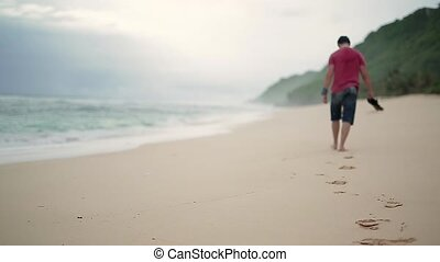Guy leaving footprints on beach - Barefoot man in a red...