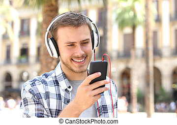 Guy listening music on line in the street - Front view of a...
