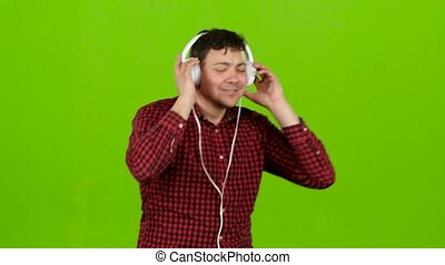 Guy listens to energetic music in headphones and dances. Green screen