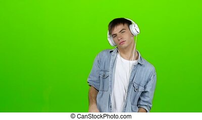 Guy listens to energetic music in headphones and dances. Green screen. Slow motion