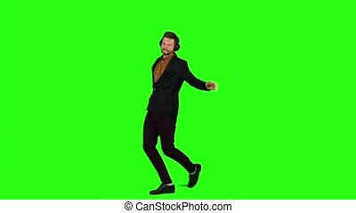 Guy listens to music in headphones and dances. Green screen. Slow motion