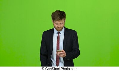 Guy looks at the photos on the phone and on the move scrolls through the list of pictures, he has a good mood, he smiles. Green screen