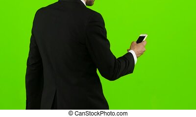 Guy looks at the photos on the phone and on the move scrolls through the list of pictures, he has a good mood, he smiles. Green screen. Back view