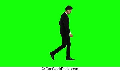 Guy looks at the photos on the phone and on the move scrolls through the list of pictures, he has a good mood, he smiles. Green screen. Side view
