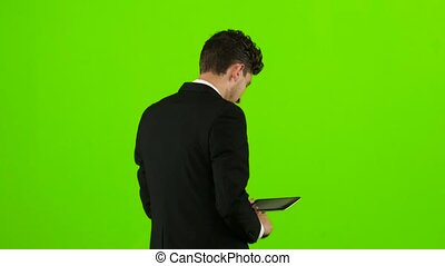 Guy looks at the photo on the phone and finds a list of pictures. Green screen. Back view