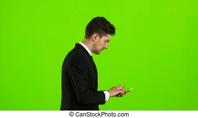 Guy looks at the photo on the phone and finds a list of pictures,. Green screen. Side view
