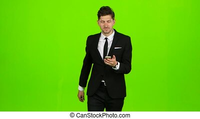 Guy looks at the photo on the phone and finds a list of pictures. Green screen