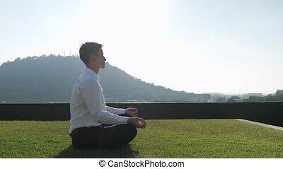 guy meditates under sunlight against green hill on terrace