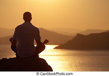 Guy meditating at sunset sitting on a rock by the sea
