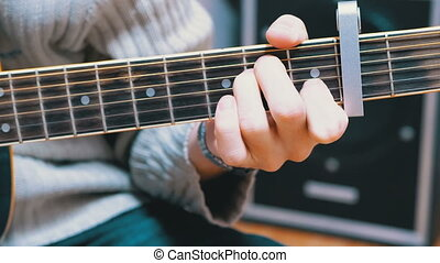 Guy Musician Plays an Acoustic Guitar. The left hand pinches...