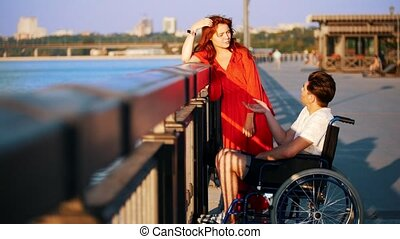 Guy On A Wheelchair And Girl With Red Hair Communicate On The Waterfront In The Summer Evening