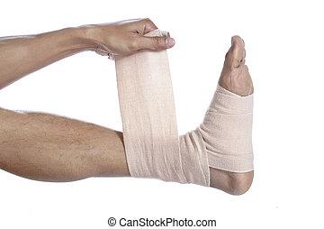 guy placing a tensor bandage on his feet