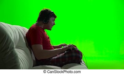 Guy playing computer games sitting on the sofa. Green screen