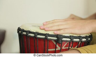 Guy playing on a hand drum close up.