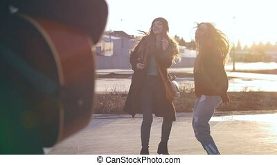 Guy playing on guitar in front of attractive dancing girls at the street