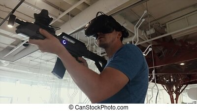 Guy playing VR sniper game with gun and glasses - Guy...