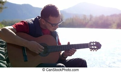 Guy plays on a guitar sitting by mountain river on sunny day...