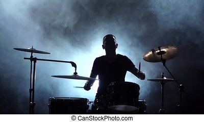 Guy plays the music on the drum. Black smoky background. Silhouettes. Side view. Slow motion