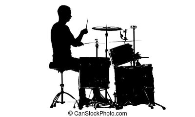 Guy plays the music on the drum. White background. Silhouettes. Side view. Slow motion