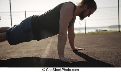 Guy presses on the court - Man doing push up exercise in...