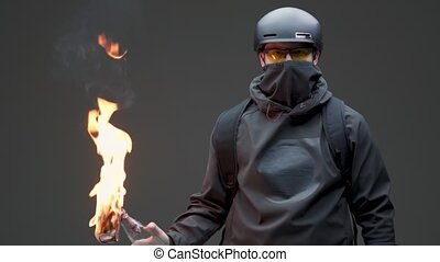 Guy protestor activist in black mask and helmet with fire Molotov cocktail on rebellion on gray studio background. High quality 4k footage