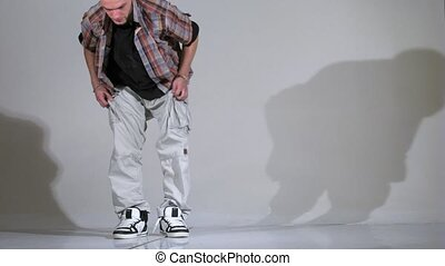 Guy-rapper in cap and in light clothes poses for  photographer