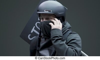 Guy rebel activist protestor in helmet and mask chatting on phone during picket or revolt on gray studio background. High quality 4k footage
