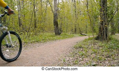 guy rides a bicycle on a footpath in the woods