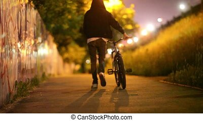 Guy rides a bike along the night alley in the city