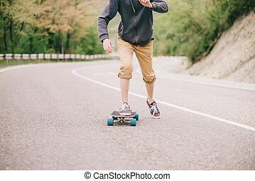 Guy riding on longboard asphalt road. - Unrecognizable guy...