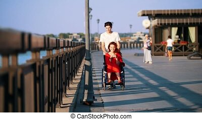 Guy Rolls A Disabled A Smiling Girl With The Red Hair In A...