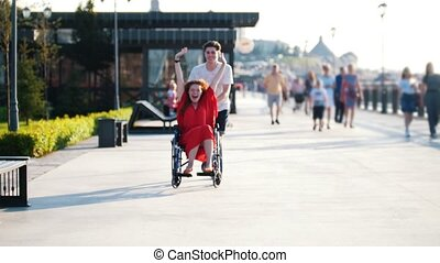 Guy Rolls A Happy Disabled Girl In A Wheelchair On The...