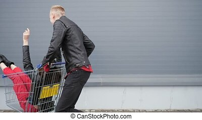 Guy rolls his attractive young girlfriend in the trolley on...