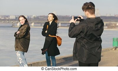 Guy shoots two funny girlfriends on the waterfront in sunny...