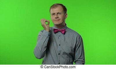 Guy showing loser gesture, pointing finger to camera, sarcastic smile, blaming for failure, lost job. Portrait of man 30s posing in shirt isolated on chroma key background in studio. People emotions