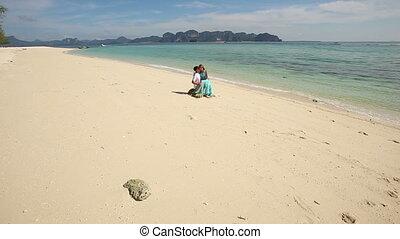 guy sits on stone with asian girl