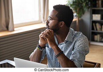 Guy sitting at table pondering over problem looking at distance