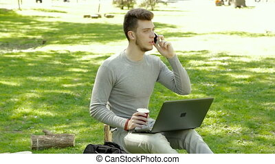 guy sitting on a tree stump in the Park talking on the phone and drinks coffee