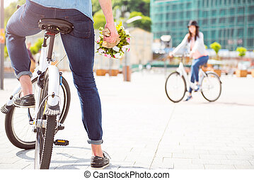 Guy sitting on bike and holding bouquet