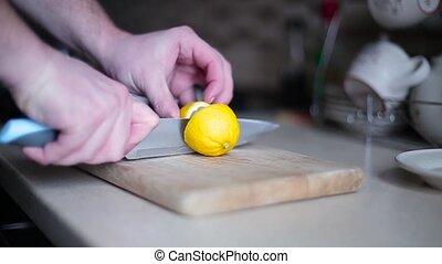 Guy sliced lemon on the board close up