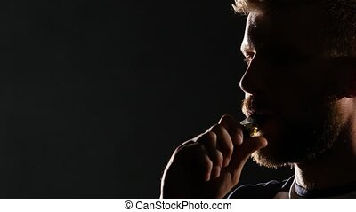 Guy smokes an electronic cigarette and exhales a lot of smoke. Black background