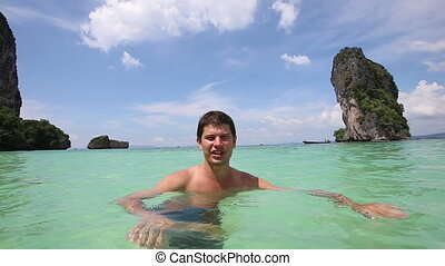 guy stands in transparent azure sea and speaks - handsome...