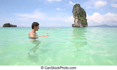 guy stands in transparent azure sea - young guy stands in...