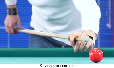 Guy in the white t-shirt takes aim, to make an impact on a billiard ball. Close up