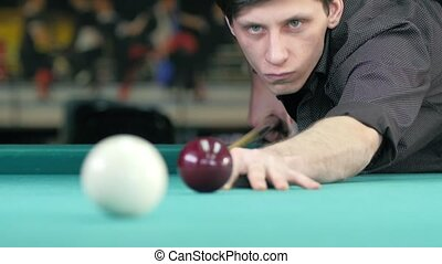Guy in the white t-shirt takes aim, to make an impact on a billiard ball. Close up. Slow motion