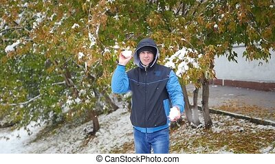 guy throws a snowball in the autumn park