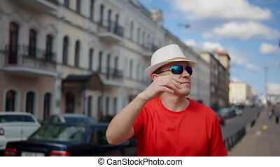 Tourist in a hat walks along a city street, inspects the surroundings, camera movement