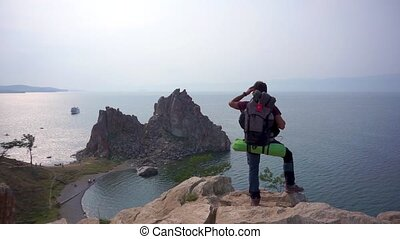 Guy-tourist stands at the edge of the cliff and looks into...
