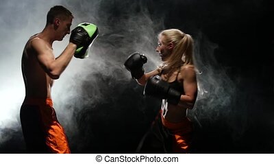 Guy trainer and the girl on the boxing paws working off the...